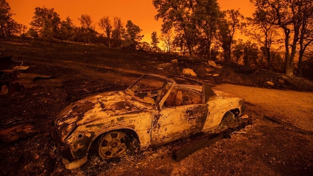 Cars scorched by the Carr Fire rest at a residence in Redding, Calif., on Friday, July 27, 2018. The fire rapidly expanded Thursday when erratic flames swept through the historic Gold Rush town of Shasta and nearby Keswick, then cast the Sacramento River in an orange glow as they jumped the banks into Redding. (AP Photo/Noah Berger)