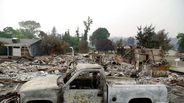 A burned out vehicle sits in front of a wildfire-ravaged home Saturday, July 28, 2018, in Redding, Calif. (AP Photo/Marcio Jose Sanchez)