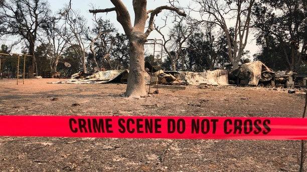 Police tape blocks the house where relatives say three people were found dead following a wildfire in Redding, Calif., Saturday, July 28, 2018. The death count from a rapidly growing Northern California wildfire rose to five Saturday after two young children and their great-grandmother who had been unaccounted for were confirmed dead. Bledsoe's two children, James Roberts, 5, and Emily Roberts, 4, were stranded with her grandmother Melody Bledsoe, 70, when fire swept through the rural area where they were staying Thursday. (AP Photo/Jonathan J. Cooper)
