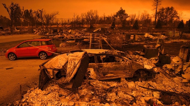 CORRECTS DATE TO JULY 27 - Two vehicles that endured the Carr Fire, one with minor cosmetic damage and one destroyed, rest among leveled homes in the Lake Keswick Estates area of Redding, Calif., on Friday, July 27, 2018. (AP Photo/Noah Berger)