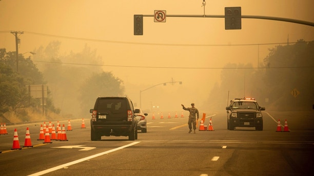 An Army National Guard specialist stands guard at a checkpoint as the Carr Fire burns in Redding, Calif., on Saturday, July 28, 2018. Thousands of residents remain evacuated as the deadly blaze threatens homes in Redding and surrounding communities. (AP Photo/Noah Berger)