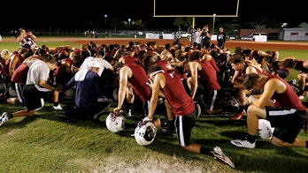 Members of the Marjory Stoneman Douglas High School football team pray together as they began practice for a new season just after midnight on Monday, July 30, 2018, in Parkland, Fla. The players, their school, and community still grieve for the 17 lives lost at the school on Feb. 14. (AP Photo/Joe Skipper)