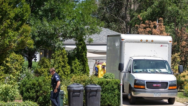 An Aurora, Colo., Police Department officer walks down the sidewalk as another officer in protective gear loads a box truck in front of the home of a man who was shot and killed by police Tuesday, July 31, 2018, in Aurora, Colo. The homeowner was shot after he killed an intruder at his home early Monday as police responded to calls for help at the home. (Phillip B. Poston/The Aurora Sentinel via AP)