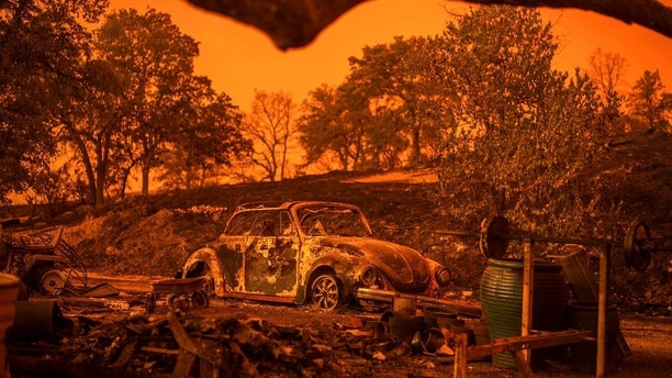 A Volkswagen Beetle scorched by a wildfire called the Carr Fire rests at a residence in Redding, Calif., Friday, July 27, 2018. (AP Photo/Noah Berger, File)