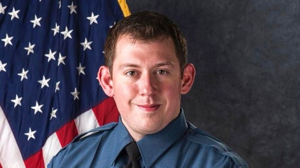 In this undated photo provided by Colorado Springs Police Department is Officer Cam Duzel. Police in Colorado Springs, Colorado say an officer who was wounded in a shootout remains in critical condition. Police said Friday, Aug. 3, 2018, that Officer Cem Duzel had movement on both sides of his body overnight and has family and friends were by his side in the hospital. He was shot while responding to a call about shots fired early Thursday east of downtown. Investigators say 31-year-old Karrar Noaman Al Khammasi pulled a handgun and began shooting at officers. (Colorado Springs Police Department via AP)