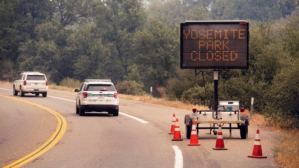 FILE - In this July 25, 2018 file photo, a sign on Highway 41 announces the closure of Yosemite National Park near Oakhurst, Calif. Yosemite National Park could reopen its scenic valley and other areas Monday, Aug. 6, 2018, if conditions improve after a 12-day closure due to nearby wildfires. The park's iconic cliffs have been shrouded in so much smoke that the air quality in Yosemite is currently worse than Beijing. (AP Photo/Noah Berger, File)