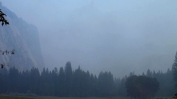 In this Wednesday, Aug. 1, 2018 image from a Yosemite Conservancy webcam, smoke from wildfires obscures the Ahwahnee Meadow at Yosemite National Park, Calif. Yosemite National Park could reopen its scenic valley and other areas Monday, Aug. 6, 2018, if conditions improve after a 12-day closure due to nearby wildfires. The park's iconic cliffs have been shrouded in so much smoke that the air quality in Yosemite is currently worse than Beijing. (Webcam by Yosemite Conservancy via AP)