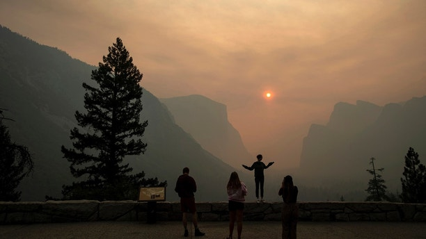 FILE - In this July 25, 2018 file photo, Hannah Whyatt poses for a friend's photo as smoke from the Ferguson fire fills Yosemite Valley in Yosemite National Park, Calif. Yosemite National Park could reopen its scenic valley and other areas Monday, Aug. 6, 2018, if conditions improve after a 12-day closure due to nearby wildfires. The park's iconic cliffs have been shrouded in so much smoke that the air quality in Yosemite is currently worse than Beijing. (AP Photo/Noah Berger, File)