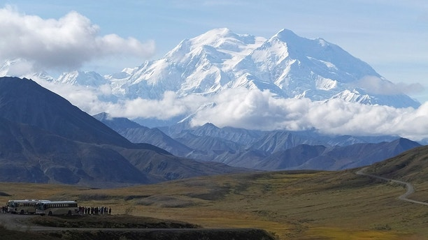 FILE - In this Aug. 26, 2016, file photo sightseeing buses and tourists are seen at a pullout popular for taking in views of North America's tallest peak, Denali, in Denali National Park and Preserve, Alaska. Rescuers are attempting to locate a sightseeing plane that crashed with the pilot and four passengers aboard high on a mountain ridge in Denali National Park and Preserve. The pilot reported on his satellite phone Saturday, Aug. 4, 2018, that there were some injuries but authorities couldn't get details before the satellite connection dropped. (AP Photo/Becky Bohrer, File)