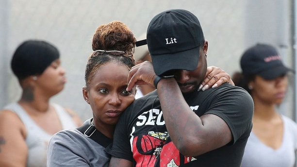 In this Sunday, Aug. 5, 2018 photo, a man wipes his eyes outside the Stroger Hospital in Chicago, after leaving the emergency room due to overwhelming crowds of family and friends of shooting victims. Police Superintendent Eddie Johnson plans to discuss the weekend violence during a Monday news conference. (Antonio Perez/Chicago Tribune via AP)