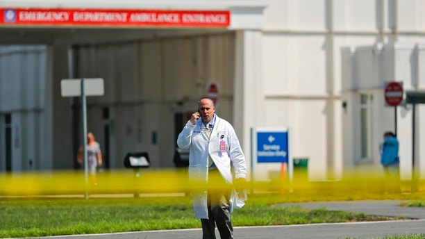 A physician walks out of the emergency entrance to Westchester Medical Center, Wednesday, Aug. 8, 2018, in Valhalla, N.Y. A man shot a female patient and then killed himself at the suburban New York hospital Wednesday, police said.(AP Photo/Julie Jacobson)