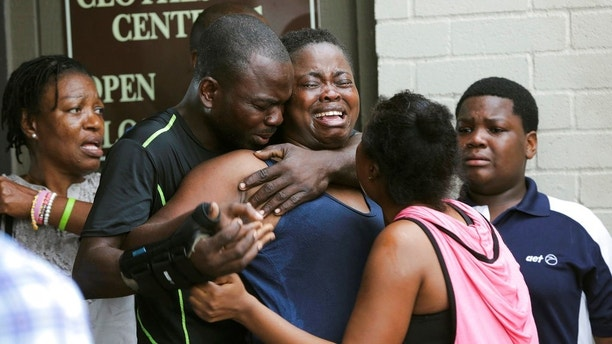 In this Saturday, Aug. 4, 2018, photo, the mother, center, of two young children is comforted after she found them stabbed to death in their father's apartment in Houston. Authorities say that Jean Pierre Ndossoka, the man suspected of fatally stabbing his two children, has been hospitalized after police found him Sunday with a self-inflicted gunshot wound in his car. Court records show he has been charged with capital murder. (Elizabeth Conley/Houston Chronicle via AP)