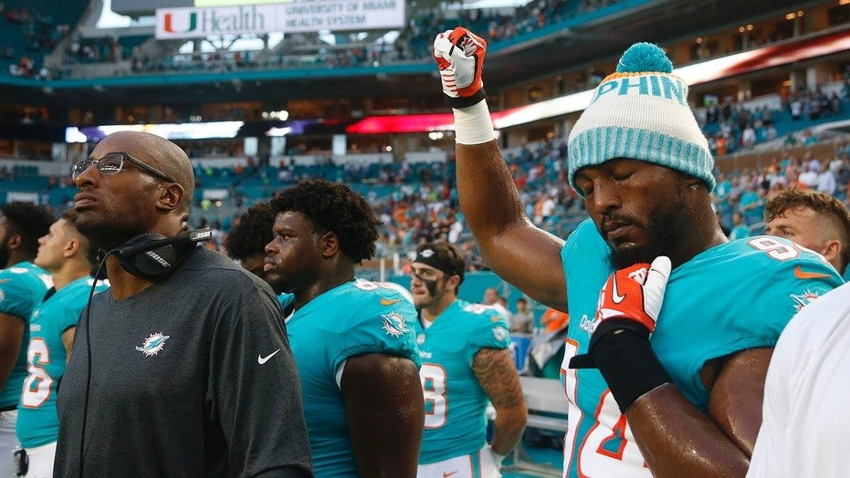Miami Dolphins defensive end Robert Quinn (94) raises his right fist during the singing of the national anthem, before the team's NFL preseason football game against the Tampa Bay Buccaneers, Thursday, Aug. 9, 2018, in Miami Gardens, Fla.