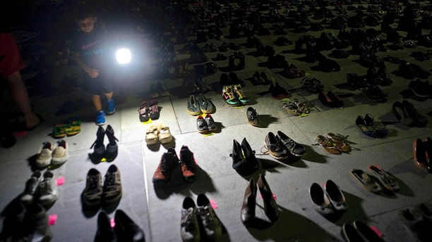 FILE - In this June 1, 2018 file photo, a child shines a light on hundreds of shoes at a memorial for those killed by Hurricane Maria, in front of the Puerto Rico Capitol in San Juan. Puerto Rico has conceded that Hurricane Maria killed more than 1,400 people on the island last year and not just the 64 in the official death toll. (AP Photo/Ramon Espinosa, File)