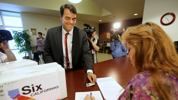 FILE - In this July 15, 2014 file photo, Silicon Valley venture capitalist Tim Draper presents his drivers license for identification purposes to Heather Ditty, elections manager for the Sacramento County Registrar of Voters, as he turns in boxes of petitions for a ballot initiative that would ask voters to split California into six separate states in Sacramento, Calif. The court struck venture capitalist Draper's initiative from the ballot in July 2018 as part of a legal challenge in response to a lawsuit but didn't rule on the merits of the case. Draper says he's giving up on the effort after the state Supreme Court knocked it off the November 2018 ballot. (AP Photo/Rich Pedroncelli, File)