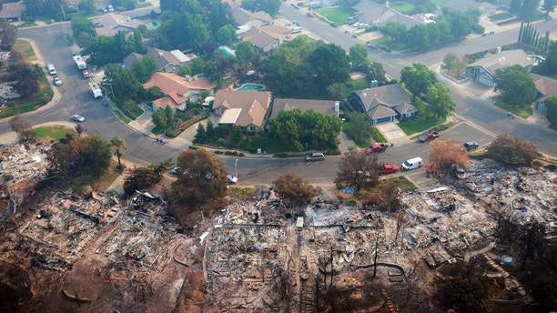 Homes destroyed by a wildfire are seen from an aerial view in the Keswick neighborhood of Redding, Calif., Friday, Aug. 10, 2018. Fire crews have made progress against the biggest blaze in California history but officials say the fire won't be fully contained until September. (AP Photo/Michael Burke)