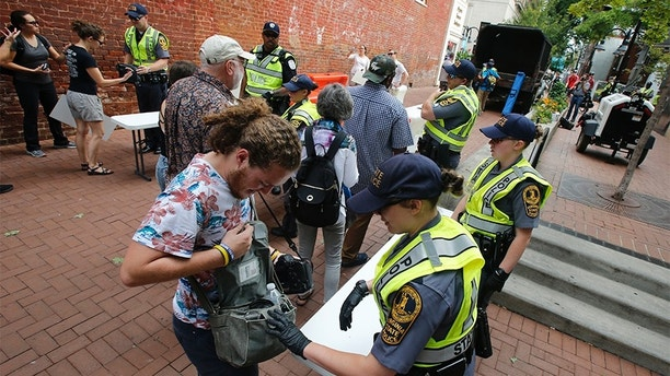 State Police inspect bags as they lock down the downtown area in anticipation of the anniversary of last year's Unite the Right rally in Charlottesville, Va., Saturday, Aug. 11, 2018. The Governor has declared a state of emergency in Charlottesville. (AP Photo/Steve Helber)