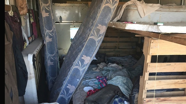 The back of a moving truck serves as sleeping quarters at a squalid makeshift living compound in Amalia, N.M., on Friday, Aug. 10, 2018. The compound offers hints about the lives of five adults and 11 malnourished children who were detained there and rescued last week. The remains of a young child were later recovered from within the compound and may resolve the fate of the missing, severely disabled boy Abdul-ghani Wahhaj. The remains haven't been positively identified by a state medical examiner. (AP Photo/Morgan Lee)