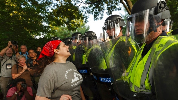 "Emily Filler attempts to dissuade state police from advancing on students rallying on the grounds of the University of Virginia on the anniversary of the ""Unite the Right"" rally in Charlottesville, Va. Saturday, Aug. 11, 2018. The city of Charlottesville plans to mark Sunday's anniversary of a deadly gathering of white supremacists with a rally against racial hatred. (Craig Hudson/Charleston Gazette-Mail via AP)"