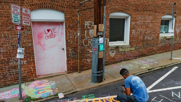 Ahmed Mohamed writes a message on the ground of the alleyway where a memorial for Heather Heyer who was killed during last year's Unite the Right rally, is located in Charlottesville, Va., Saturday, Aug. 11, 2018. The city of Charlottesville plans to mark Sunday's anniversary of a deadly gathering of white supremacists with a rally against racial hatred. (Craig Hudson/Charleston Gazette-Mail via AP)
