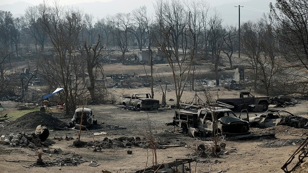 Burned out cars sit in a neighborhood burned in the Carr Fire, Saturday, Aug. 11, 2018, in Redding, Calif. (AP Photo/John Locher)
