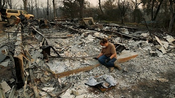 Kim Burns sifts through the charred rubble of her home burned in the Carr Fire, Sunday, Aug. 12, 2018, in Redding, Calif. (AP Photo/John Locher)