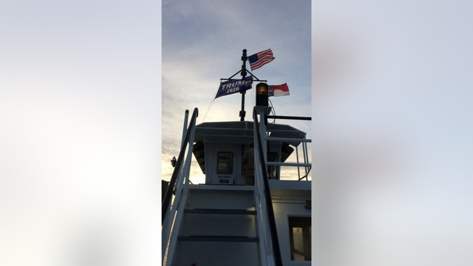 "Two North Carolina state workers were suspended for a week without pay after flying a large ""Trump 2020"" flag atop an Outer Banks ferry in July."