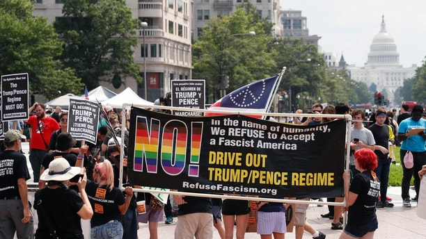 "Groups protest in Freedom Plaza with the U.S. Capitol in the background, on the one year anniversary of Charlottesville's ""Unite the Right"" rally, Sunday, Aug. 12, 2018, in Washington. (AP Photo/Alex Brandon)"