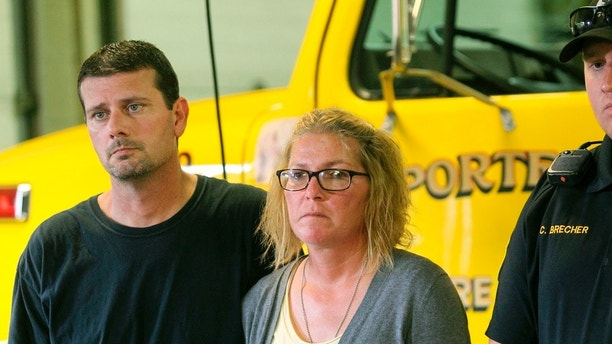 Jeremy Neiswonger, stepfather of Jake Wilson, and Megan Neiswonger, Wilson's mother, listen during a press conference at the La Porte City Fire Department on Thursday, Aug. 16, 2018, in La Porte City, Iowa. Human remains recovered from a creek this week are believed to be those of Wilson, a 16-year-old autistic boy who vanished from his small Iowa hometown in April, authorities said Thursday. (Jeff Reinitz /The Courier via AP)
