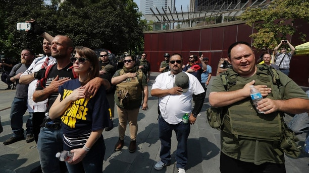 Supporters of a rally held by members of the Patriot Prayer and other weapon rights groups during a recording of the national anthem, Saturday, August 18, 2018, at Seattle City Hall. (AP Photo / Ted S. Warren)