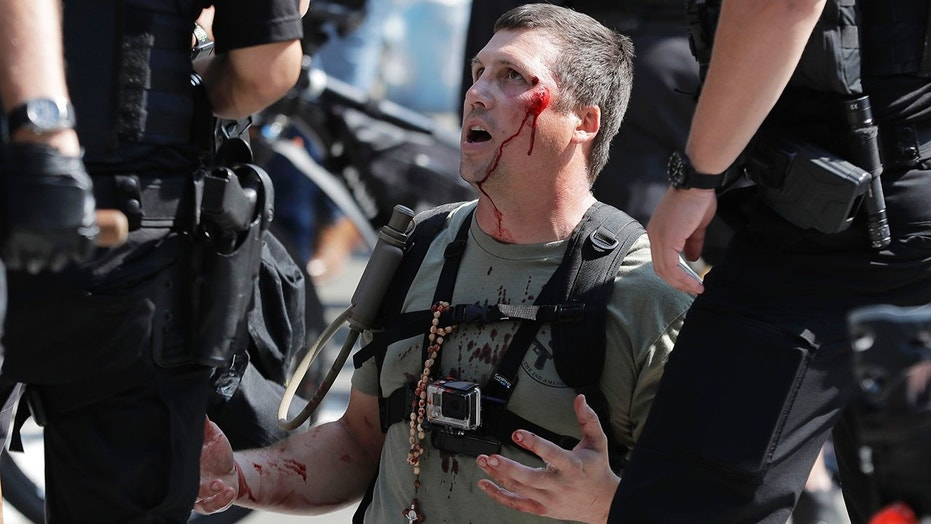A man protesting with Patriot Prayer and other groups supporting gun rights is being treated for injury during a rally and counter-protest in Seattle, 18 August 2018.