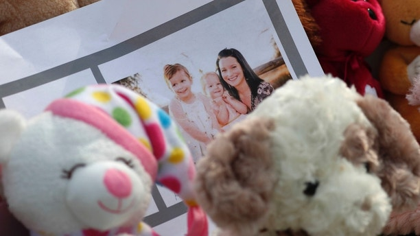A photograph sits amid the tributes as they grow outside the home where a pregnant woman, Shanann Watts, and her two daughters, Bella and Celeste, lived Thursday, Aug. 16, 2018, in Frederick, Colo. The woman's husband, Christopher Watts, has been arrested on suspicion of killing his family. (AP Photo/David Zalubowski)
