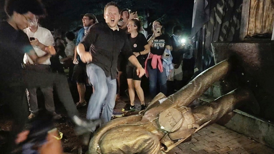 "Aug. 20: Protesters celebrate after the Confederate statue known as ""Silent Sam"" was toppled on the campus of the University of North Carolina in Chapel Hill."