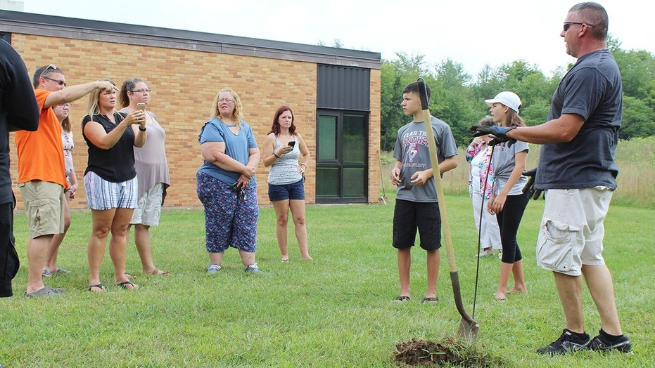 In this Sunday, Aug. 26, 2018, photo classmates that were in the AWARE classes at Coloma Junior High School in 1988 try to find a time capsule that they buried behind the school in Coloma, Mich., that year. The Herald-Palladium reports that the seven classmates and two teachers spent two hours on Sunday digging outside Coloma Junior High in southwestern Michigan.