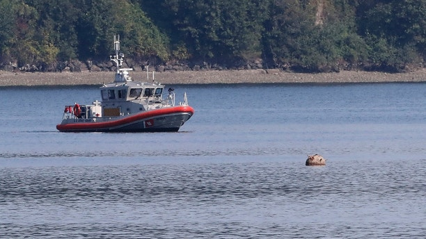 "A U.S. Coast Guard boat keeps watch over a ""reported unexploded ordnance"" drifting in the water between Brownsville Marina and Bainbridge Island, off Brownsville, Wash., Tuesday, Aug. 28, 2018. Brownsville is located a few miles south of Naval Base Kitsap - Keyport's torpedo testing range. The Navy was not immediately able to respond to a request for information. (Meegan M. Reid/Kitsap Sun via AP)"