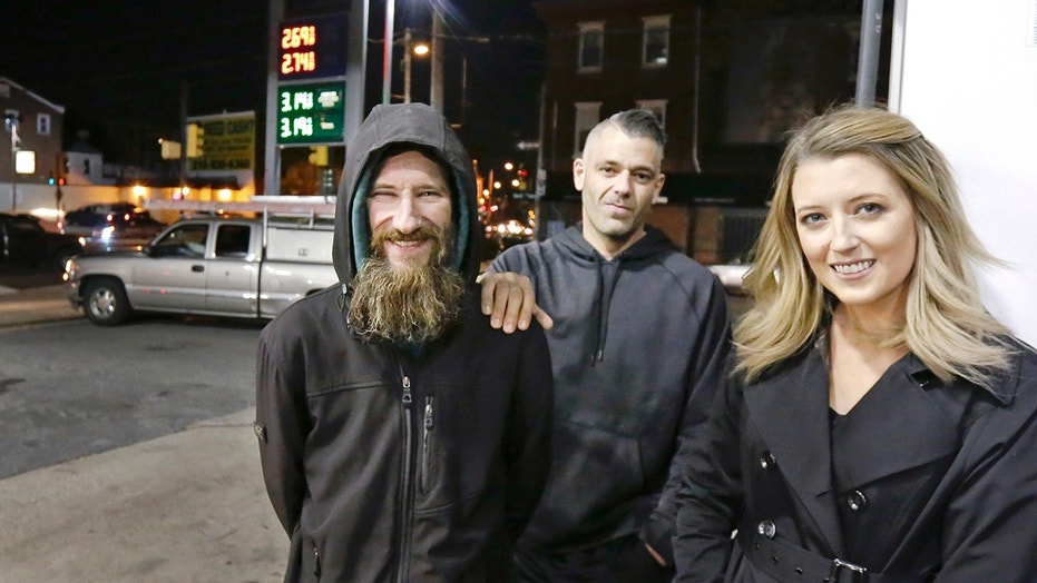 Johnny Bobbitt Jr., left, Kate McClure, right, and McClure's boyfriend Mark D'Amico pose at a gas station in Philadelphia, Nov. 17, 2017. When McClure ran out of gas, Bobbitt, who is homeless, gave his last $20 to buy gas for her. McClure started a GoFundMe.com campaign for Bobbitt.