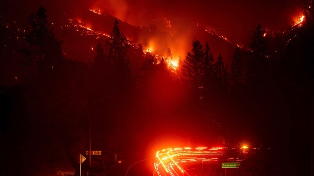 Fire trucks pass the Delta Fire burning in the Shasta Trinity National Forest Calif. on Wednesday Sept. 5 2018. Parked trucks lined more than two miles of Interstate 5 as both directions remained closed to traffic