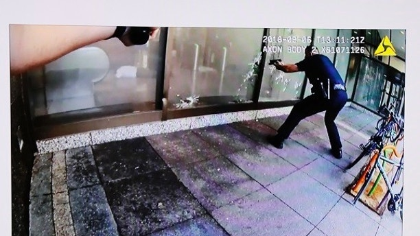 Suspect Omar Enrique Santa Perez lies on the ground, seen behind glass of left window pane, after being engaged by police as seen on police body camera video displayed during a news conference detailing the shooting incident of the previous day in the downtown business district, Friday, Sept. 7, 2018, in Cincinnati. Cincinnati Police Chief Eliot Isaac and Mayor John Cranley addressed the media. (Cincinnati Police via AP)