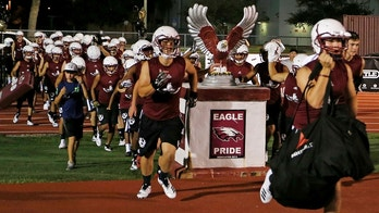 Members of the Marjory Stoneman Douglas High School football team take the field to begin practice for a new season just after midnight on Monday, July 30, 2018, in Parkland, Fla. The players, their school, and community still grieve for the 17 lives lost at the school on Feb. 14. (AP Photo/Joe Skipper)