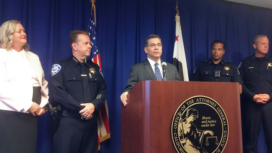 California Attorney General, Xavier Becerra, at podium, and other officials announce indictments of 32 members of purported street gangs on charges of stealing more than $1 million using an unusually sophisticated credit card fraud, at a news conference in Sacramento, Calif., Monday, Sept. 10, 2018. From left are Deputy Attorney General Tawnya Austin, who heads the attorney general's e-crimes unit; Walnut Creek Police Chief Tom Chaplin; Becerra; Sacramento Police Chief Daniel Hahn; and Vacaville Police Chief John Carli. Authorities said Monday that the BullyBoys and the CoCo Boys street gangs defrauded hundreds of victims across Northern California by breaking into dozens of medical and dental offices to steal credit card terminals and patient records. (AP Photo/Don Thompson)