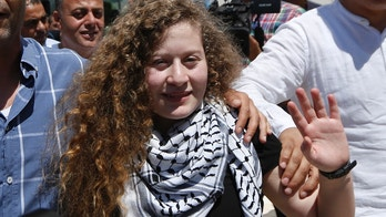 File - In this , Sunday, July 29, 2018 file photo, Ahed Tamimi waves after she visited the tomb of former Palestinian leader Yasser Arafat in the West Bank city of Ramallah. Tamimi family says they have been banned from traveling abroad. Her father, Bassem, said they were informed by the Palestinian Ministry of Civil Affairs they are barred by the Israeli Authorities from leaving. He said they were set to leave last week upon initiation by pro-Palestinian groups in Belgium, France and Spain. (AP Photo/Majdi Mohammed. File)