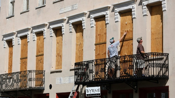 CORRECTS DATE - Derek Mundy, left, and Kris Crouse boards up the Confederate House in preparation for Hurricane Florence in downtown Charleston, S.C., Tuesday, Sept. 11, 2018. (AP Photo/Mic Smith)
