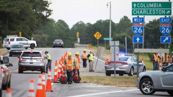 A South Carolina state trooper directs traffic as D.O.T. workers move cones at an access ramp to I-26 Tuesday, Sept. 11, 2018, in Columbia, S.C. A lane reversal was implemented earlier in the day, utilizing all lanes for travel west between Charleston and Columbia in anticipation of the arrival of Hurricane Florence. (AP Photo/Sean Rayford)