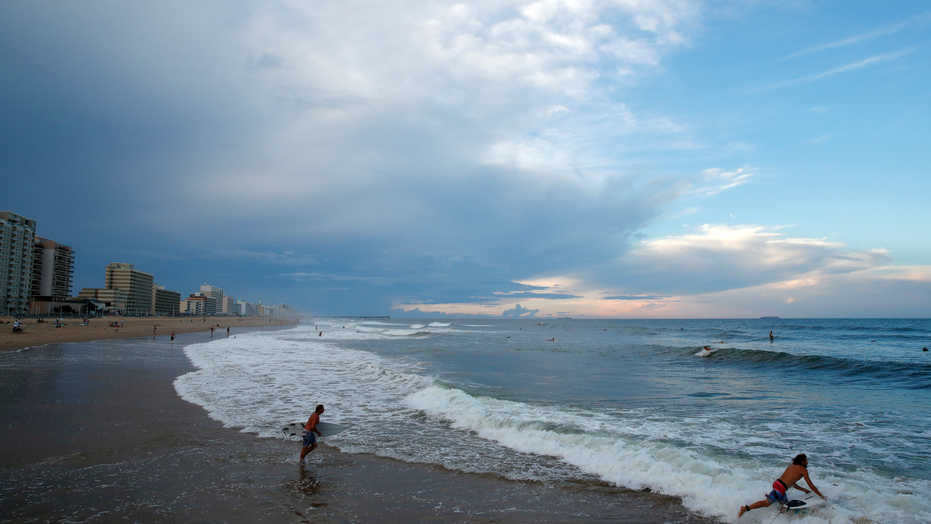 Surfers head to the waves, Tuesday, Sept. 11, 2018, in Virginia Beach, Va., before the arrival of Hurricane Florence. (AP Photo/Alex Brandon)
