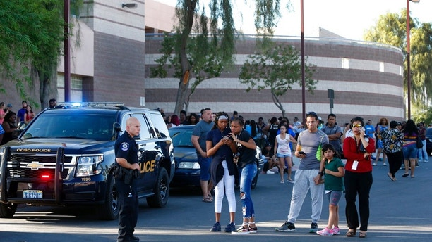 Students and parents wait outside Canyon Springs High School in North Las Vegas after a fatal shooting near a school ball field Tuesday, Sept. 11, 2018. School was out at the time of the shooting but many students were taking part in after-school activities, police said.  (Steve Marcus /Las Vegas Sun via AP)