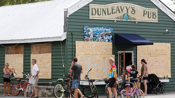 With most people off work and it looking like the Charleston, S.C., area will be spared from destructive winds many people biked to Dunleavy's Pub, one of the few open restaurants, on Sullivan's Island, S.C., as Hurricane Florence spins out in the Atlantic ocean Thursday, Sept. 13, 2018. (AP Photo/Mic Smith)
