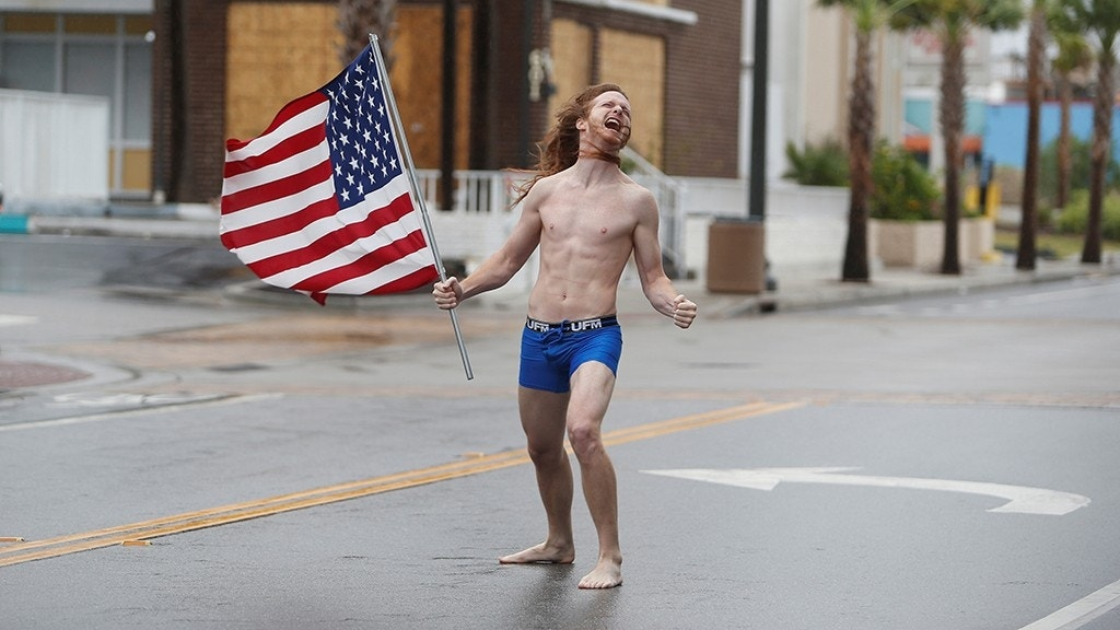 Shirtless man stares down Hurricane Florence with American flag in hand: 'Just being free and American'