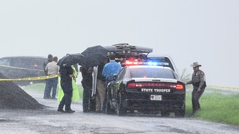 """Law enforcement officers gather near the scene where the body of a woman was found near Interstate 35 north of Laredo, Texas on Saturday, Sept. 15, 2018. A U.S. Border Patrol agent suspected of killing four women was arrested early Saturday after a fifth woman who had been abducted managed to escape from him and notify authorities, law enforcement officials said, describing the agent as a """"serial killer."""" (Danny Zaragoza/The Laredo Morning Times via AP)"""