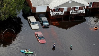 A man paddles a kayak in a flooded neighborhood in the aftermath of Hurricane Florence, in Fayetteville, N.C., Monday, Sept. 17, 2018. (AP Photo/Gerald Herbert)