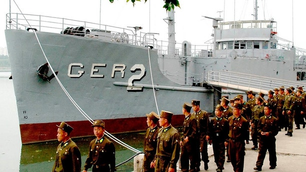 FILE - In this June 22, 2006, file photo released by the North Korean government, North Korean soldiers watch USS Pueblo, which was seized by North Korean navy off the Korean coast near Taedonggang river in Pyongyang, North Korea. In January 1968, North Korean navy boats attacked and captured the USS Pueblo off the North's east coast. (Korean Central News Agency/Korea News Service via AP, File)
